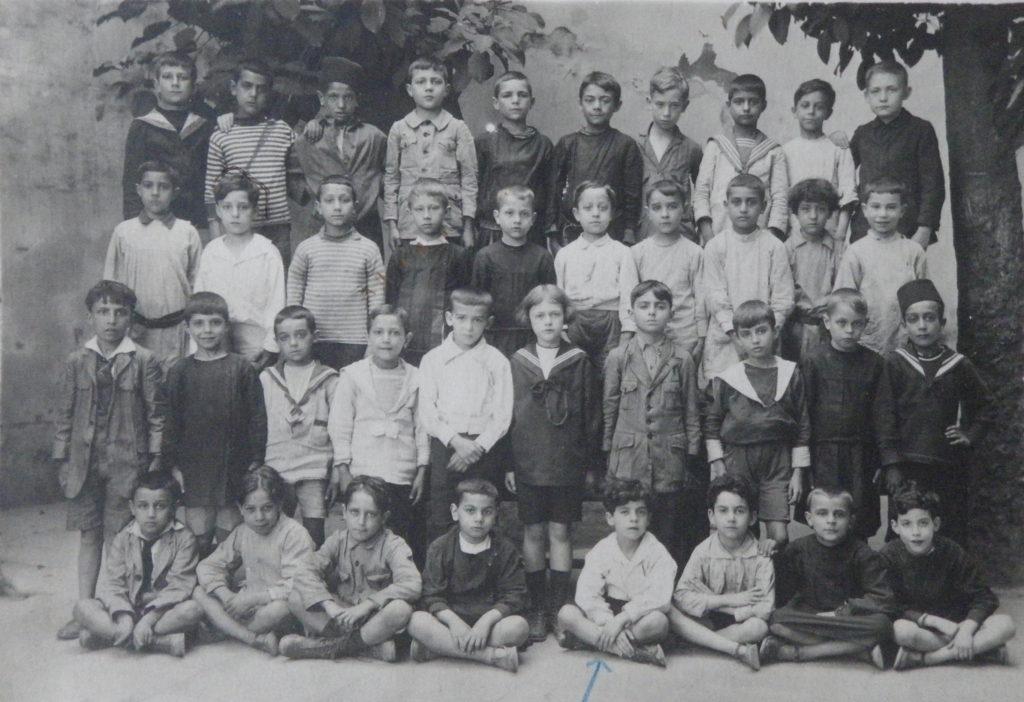 """École Mailhes du boulevard Gambetta, Alger, vers 1920. Lucien Hanoun est au troisième rang, second en partant de la gauche. Sa classe compte deux enfants """"musulmans"""", distingués par leur couvre-chef."""